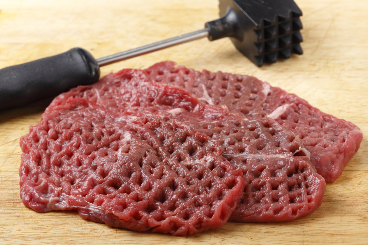 Three raw minute steaks displayed next to a meat mallet after being pounded and tenderised